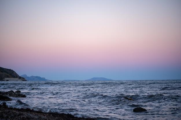 Różowe i błękitne niebo na zachód słońca. minimalistyczne tło wybrzeża