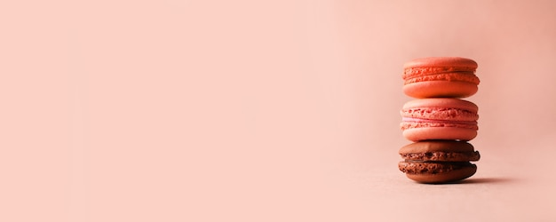 Różowe i brązowe francuskie makaroniki deserowe na pastelowym różowym tle z copyspace, widok z boku