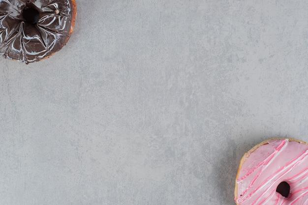Różowe i czekoladowe pączki na betonowej powierzchni