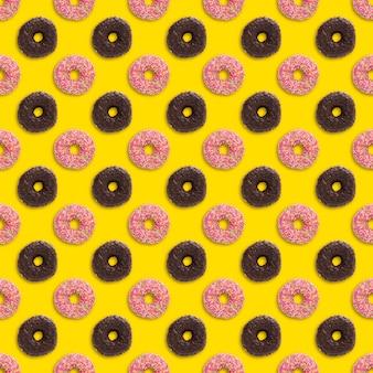 Różowe i czekoladowe pączki z posypką wzór na żółtym tle