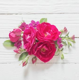 Różowe i czerwone róże na białym drewnianym tle