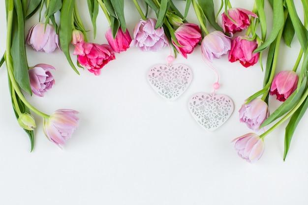 Różowe i fioletowe tulipany są wyłożone ramką i dwoma różowymi sercami
