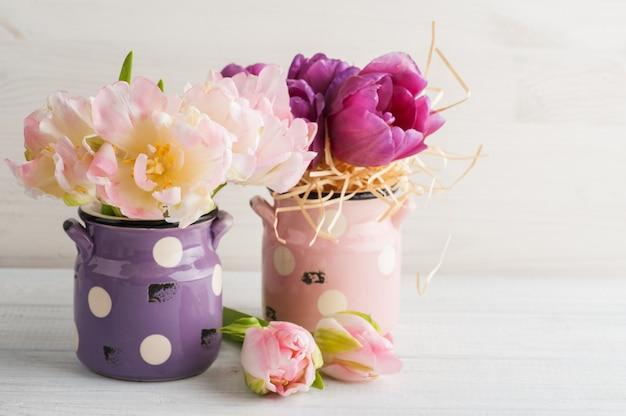 Różowe i fioletowe tulipany w uroczych glinianych doniczkach