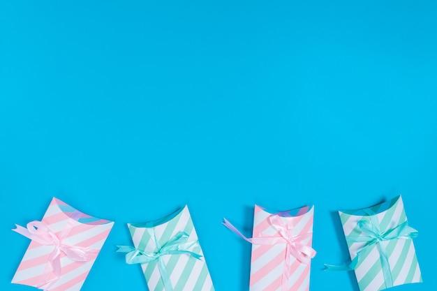 Różowe i jasnozielone pudełka upominkowe umieszczone na niebieskim tle