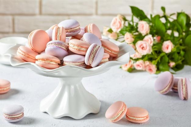 Różowe i lawendowe makaroniki na porcelanowym stojaku na ciasto i na stole. piękny bukiet róż na powierzchni ceglanego muru, widok poziomy, zbliżenie