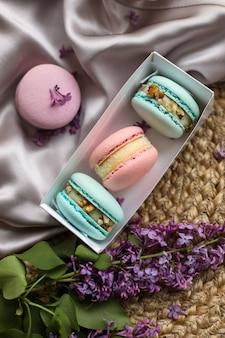 Różowe i miętowe francuskie makaroniki lub ciasteczka makaroniki w pudełku prezentowym i kwiaty bzu na tle stoiska z tkaniny i słomy. naturalne aromaty owocowo-jagodowe, kremowe nadzienie na walentynki, dzień matki.