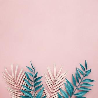 Różowe i niebieskie liście na różowym tle z copyspace na wierzchu