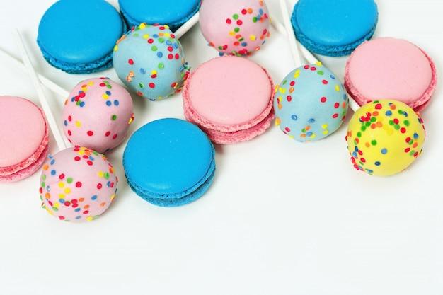 Różowe i niebieskie makaroniki i ciasto wyskakuje na białym tle z miejsca na kopię. różne ciasteczka.