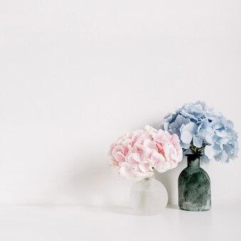 Różowe i niebieskie pastelowe bukiety kwiatów hortensji na białej powierzchni