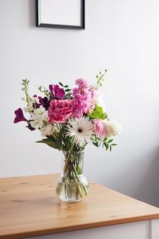 Różowe i pastelowe białe kwiaty w nowoczesnym szklanym wazonie na drewnianym stole na szarym tle ściany w pionie