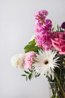 Różowe i pastelowe białe kwiaty w nowoczesnym szklanym wazonie na szarym tle ściany pionowe zbliżenie