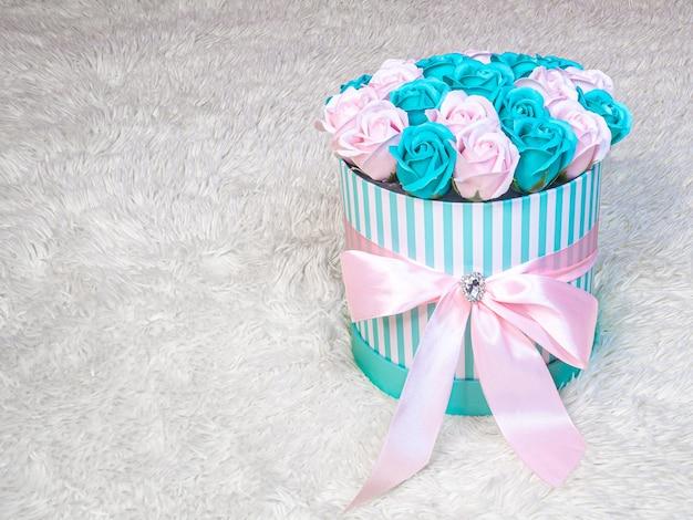 Różowe i turkusowe róże w cylindrycznym pudełku w paski przewiązane różową jedwabną wstążką na białym futrze obraz tła na walentynki i międzynarodowy dzień kobiet