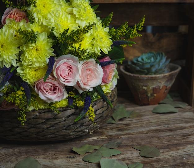 Różowe i żółte kwiaty w bambusowym wazonie.