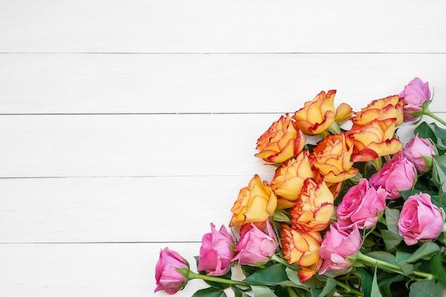 Różowe i żółte róże na białym drewnianym tle.