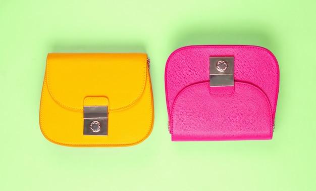 Różowe i żółte skórzane mini torebki na zielonym tle. koncepcja mody minimalizmu. widok z góry