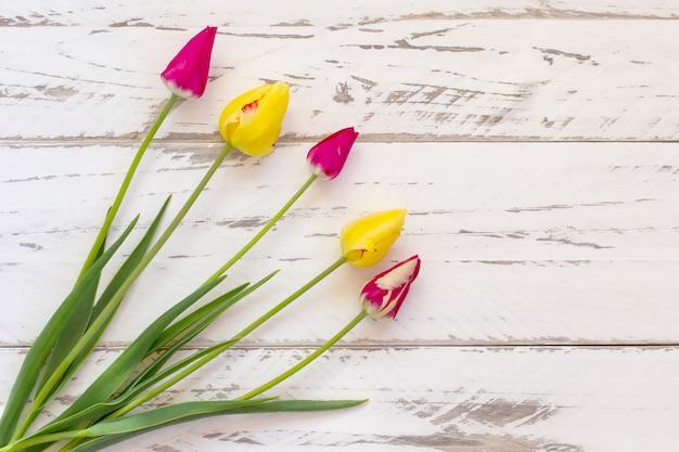 Różowe i żółte tulipany na drewnianym tle. wiosna kartkę z życzeniami z miejsca na kopię.