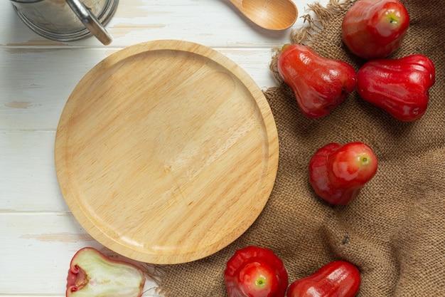 Różowe jabłko na białej powierzchni drewnianych