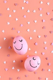 Różowe jajka z malowanymi uśmiechami na tle z serca, kartkę z życzeniami wesołych świąt.