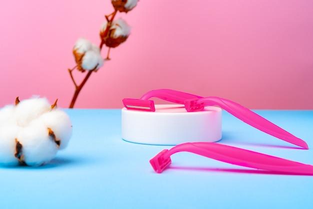 Różowe jednorazowe maszynki do golenia i kwiat bawełny na niebieskim papierze