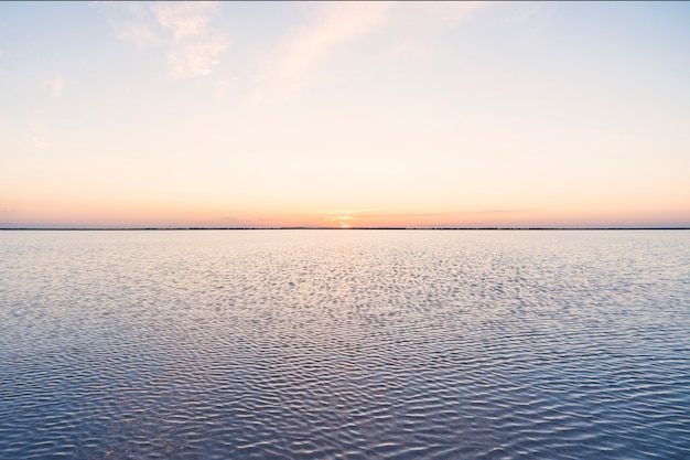 Różowe jezioro. efektownie czerwony basen używany do produkcji soli w pobliżu rio lagartos, meksyk, jukatan. słońce zachodzi na horyzoncie ha na różowo-fioletowym niebie.