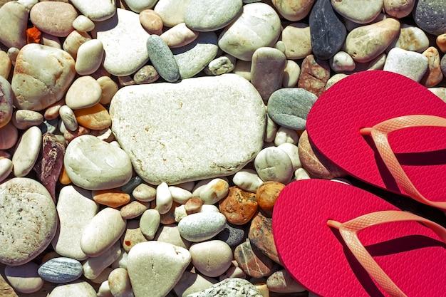 Różowe klapki na kamienistej plaży. koncepcja wakacje morze lato. widok z góry.