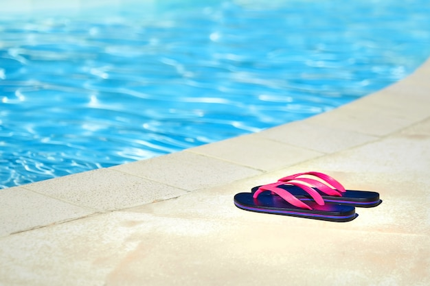 Różowe klapki przy basenie z błękitną wodą. letni ośrodek wczasowy. buty plażowe