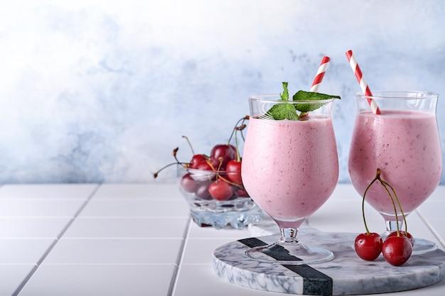 Różowe koktajle wiśniowe ze świeżymi czerwonymi jagodami, nasionami chia, zielonymi liśćmi mięty, białym kamiennym tle kuchni. selektywne skupienie.
