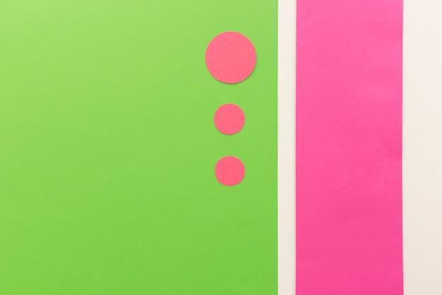 Różowe koła kształtują papiery w różnych rozmiarach układających się na zielonym papierze kartkowym