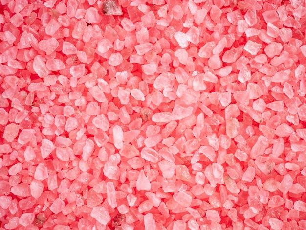 Różowe kolorowe kryształy soli jako tło. aromatyczna sól do kąpieli różana o zapachu liczi i paczuli. duże, posypane kryształkami karmazynowej soli morskiej. koncepcja pielęgnacji ciała i urody. ścieśniać.
