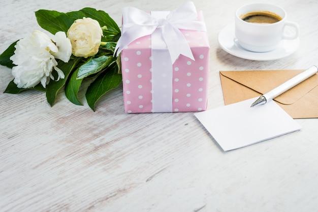 Różowe kropkowane pudełko, puste kartkę z życzeniami, koperta kraft, bukiet piwonii i filiżanka kawy na białym drewnianym stole rustykalnym.