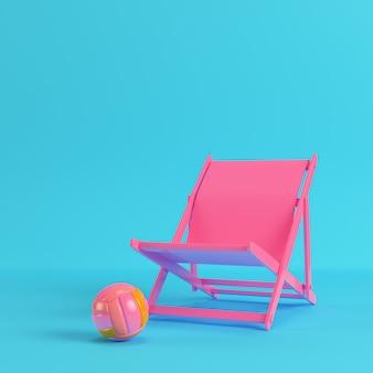 Różowe krzesło plażowe z piłką do siatkówki na jasnym niebieskim tle w pastelowych kolorach