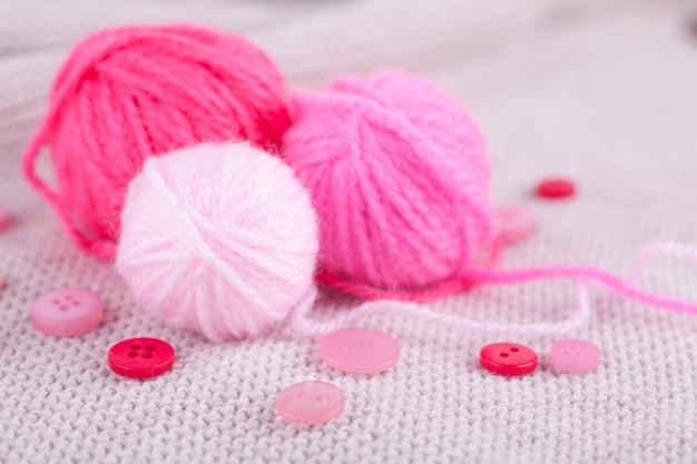 Różowe kulki przędzy o różnych rozmiarach i guziki na szarym kocie z dzianiny