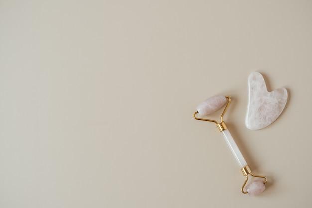 Różowe kwarcowe narzędzie do masażu gua sha i jadeitowy wałek na beżu