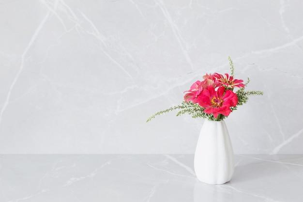 Różowe kwiaty cyni na wazonie na marmurowym tle