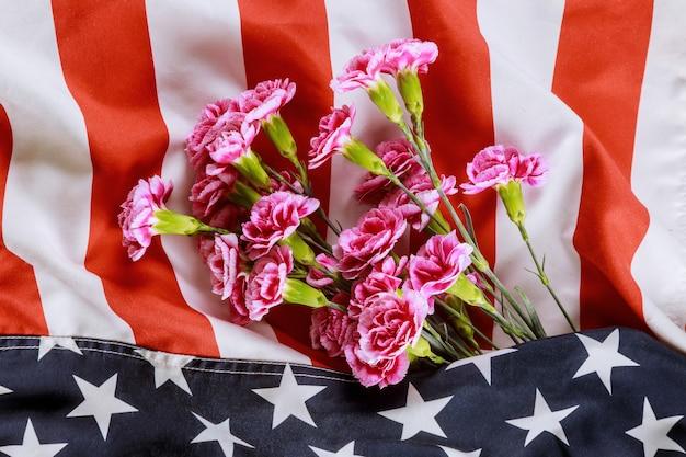 Różowe kwiaty goździków w flagi usa na tle, pamięci weteranów i dnia pamięci