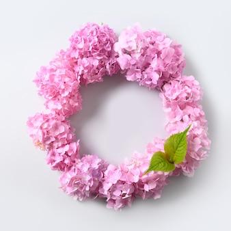 Różowe kwiaty hortensji jako wieniec na szarym tle. widok z góry. koncepcja miłości. miejsce na tekst. kreatywna kartka z życzeniami na dzień matki. szablon karty wiosny.