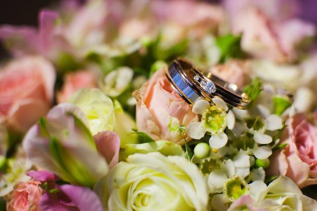 Różowe kwiaty i dwie złote obrączki ślubne