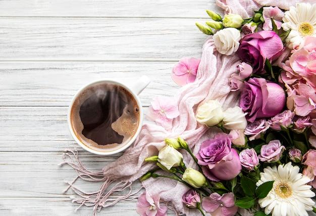 Różowe kwiaty i filiżankę kawy na białym tle drewnianych