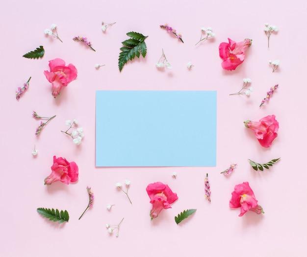 Różowe kwiaty i papier na jasnoróżowym tle widok z góry