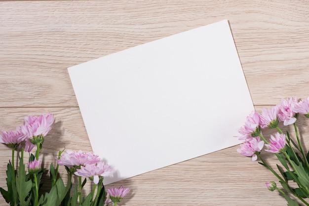 Różowe kwiaty i pusty papier do tekstu na drewnianym tle