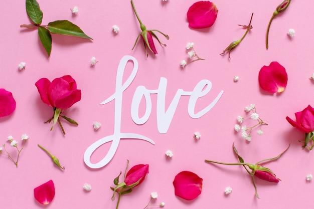 Różowe kwiaty i tekst love na jasnoróżowym tle widok z góry