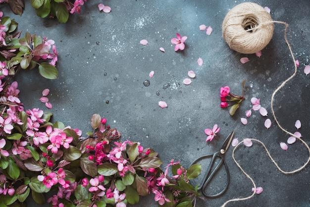 Różowe kwiaty kwitnących drzew owocowych z akcesoriami do florystyki na stole vintage.