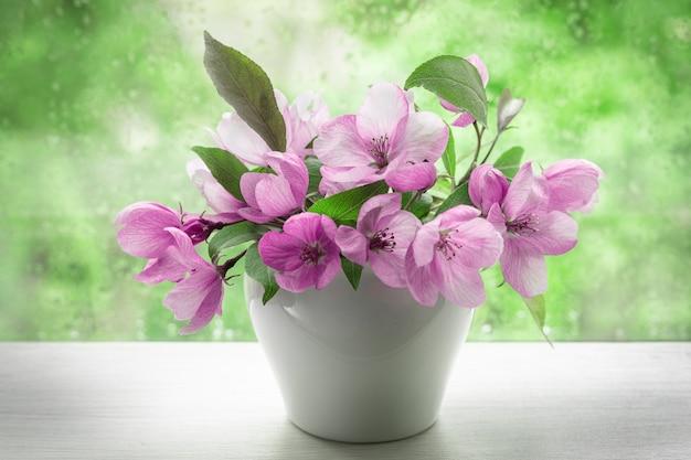 Różowe kwiaty ozdobne jabłoni w małym białym wazonie na parapecie. obraz do projektu pocztówki, kalendarz, okładka książki. zbliżenie, selektywne focus.