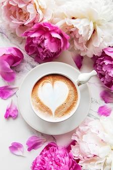 Różowe kwiaty piwonii i filiżankę kawy
