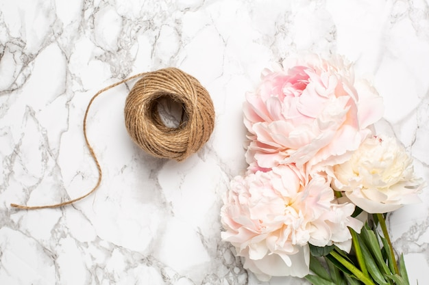Różowe kwiaty piwonii i sznurka na marmurowej powierzchni. przedmiot świąteczny i letni.