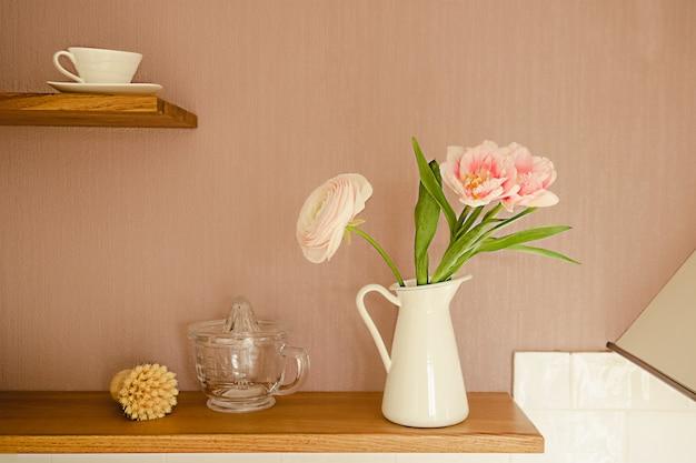 Różowe kwiaty ranunkulus w białym dzbanku na drewnianej półce nad balustradą kuchenną na ścianie. pomysły na przechowywanie i organizację kuchni.