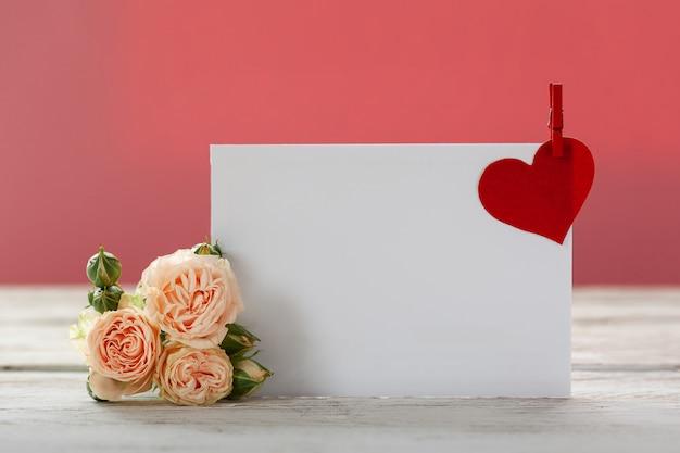 Różowe kwiaty róż z kartą upominkową i czerwonym sercem na różowym papierze