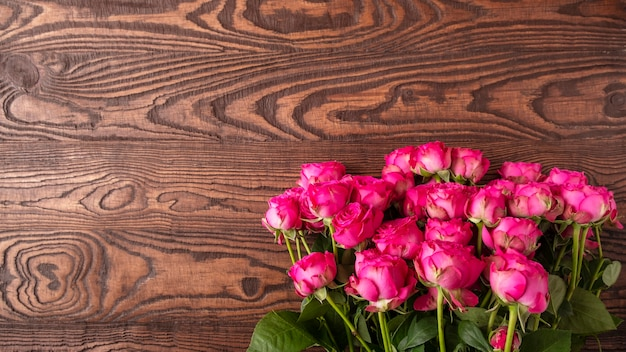 Różowe kwiaty róży na powierzchni drewnianych