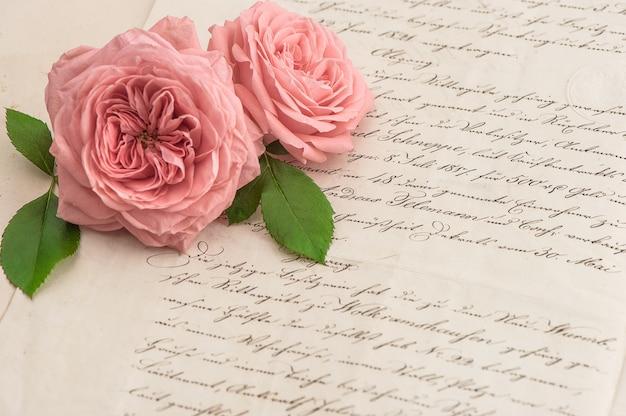Różowe kwiaty róży nad antyczny list odręczny. romantyczne tło. selektywne skupienie
