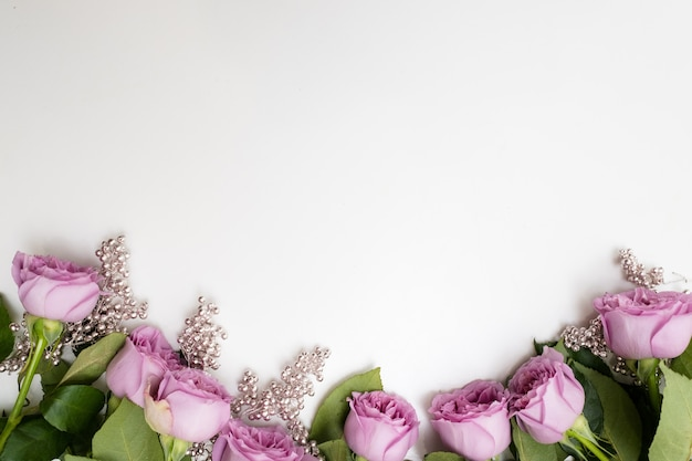 Różowe kwiaty różyczki na białym tle z ozdobą srebrnych koralików. eleganckie tło dla kobiet lub na dzień matki. koncepcja copyspace
